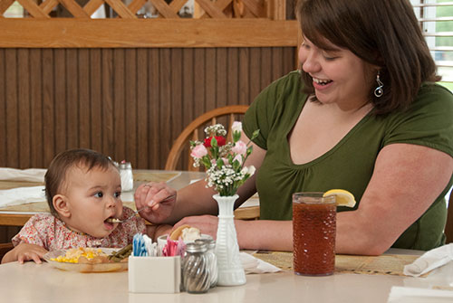 Mother feeding baby from plate at restaurant