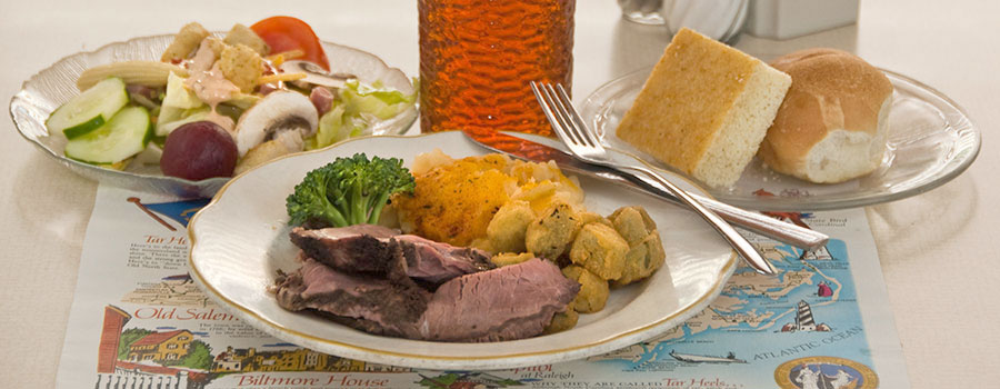 dinner plate with roast beef and vegetables, salad, rolls and tea