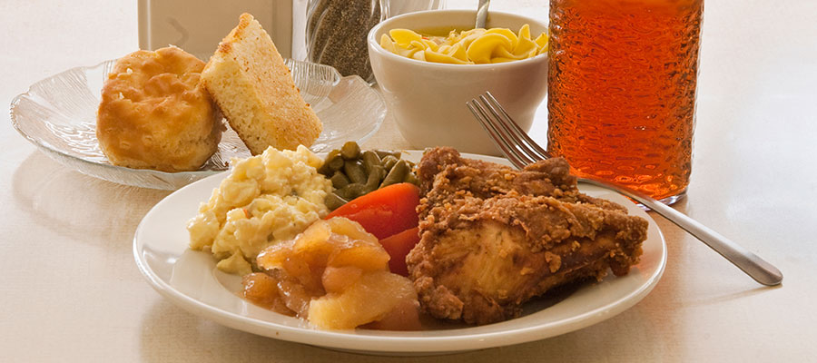 dinner plate of fried chicken, vegetables, cornbread and dessert