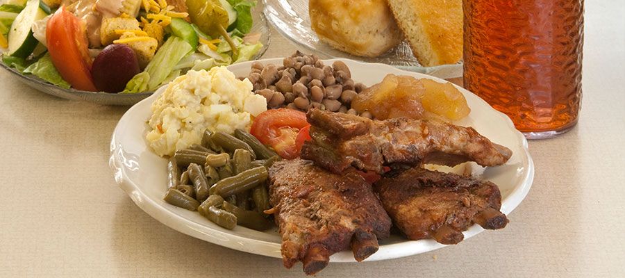 plate of ribs, vegetables with salad and cornbread and tea