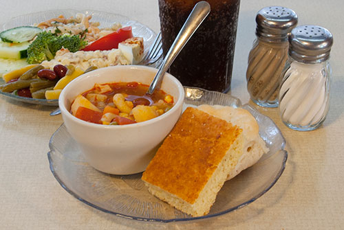 homemade cup of soup with cornbread, salad and drink